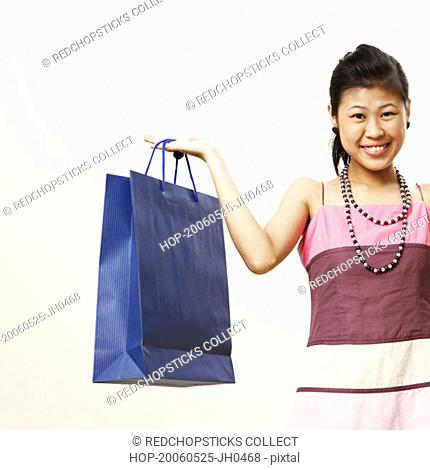 Portrait of a young woman holding shopping bags and smiling