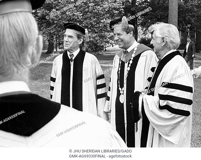 Three-quarter length portrait of three men at 1980 Johns Hopkins commencement, photo shot over the shoulder of another man, smiling facial expressions