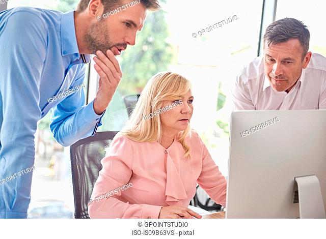 Colleagues in office with computer having discussion