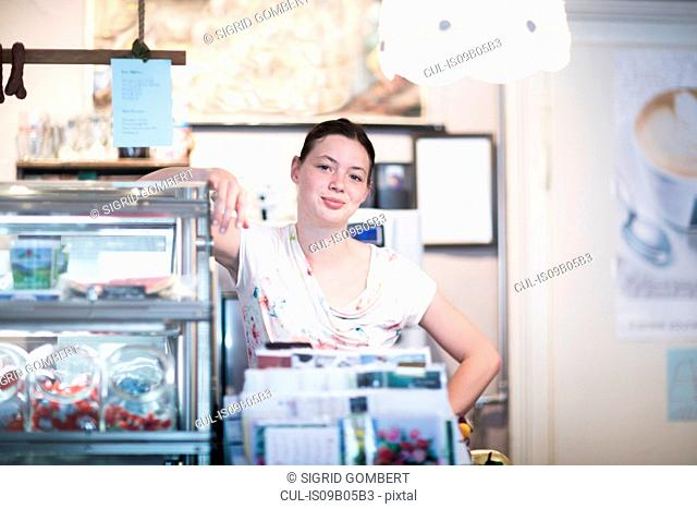 Portrait of young female shop assistant leaning on corner shop counter