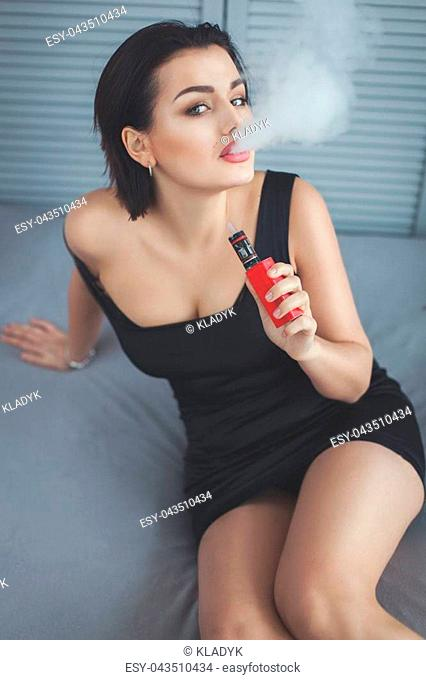 Woman lets out smoke from the electric cigarette, it looks sexy