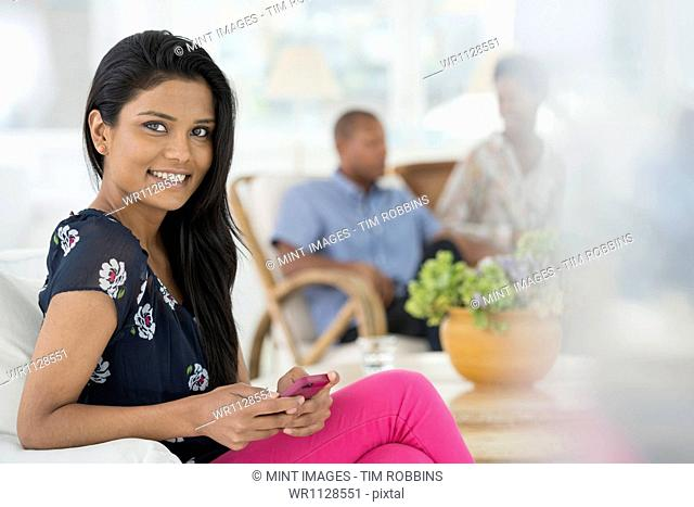 A group of people gathering together for a party or an office event. A woman seated on the sofa using her smart phone