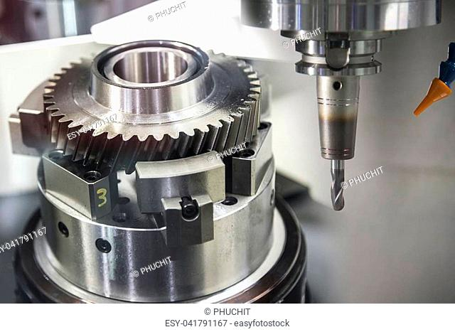 The CNC milling machine cutting the sample gear part.The mechanical part manufacturing process by CNC milling machine.Modern manufacturing process