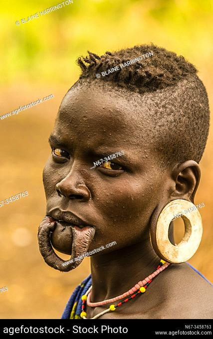 Mursi tribe woman with lower lip and earlobe modifications to hold clay discs , Mago National Park, Omo Valley, Ethiopia