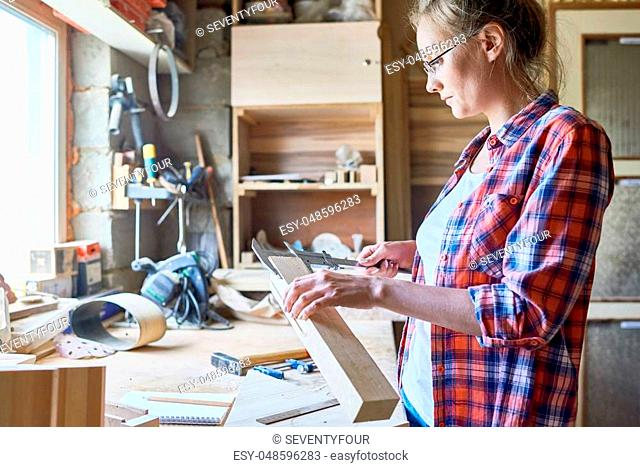 Side view portrait of modern female carpenter measuring wooden part making furniture over working table in workshop