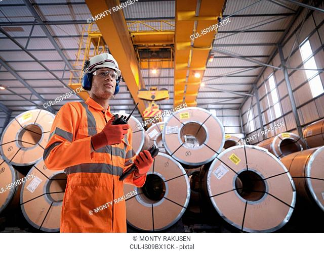Composite image of worker with rolls of steel in port depot