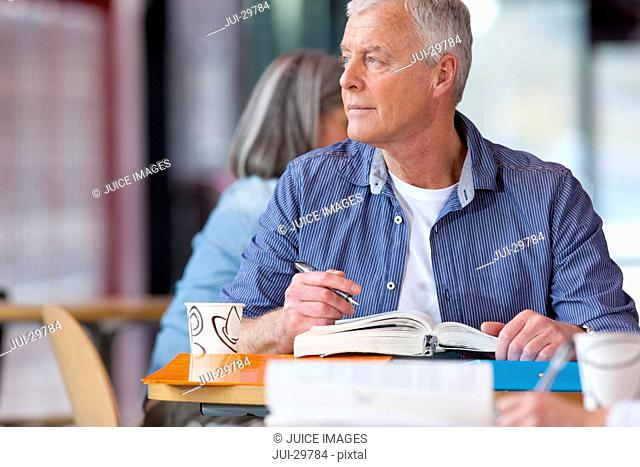 Serious mature student thinking and sitting with textbook