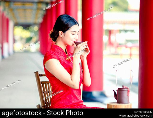 beautiful Asian woman in old traditional Chinese dresses drinking tea in the Temple