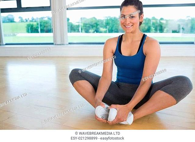 Smiling woman doing bound angle yoga pose on floor of fitness studio