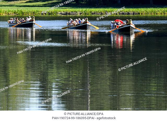 24 July 2019, Saxony-Anhalt, Wörlitz: In sunny weather, gondolas travel across Lake Wörlitz on their summer route in the UNESCO World Cultural Heritage Garden...