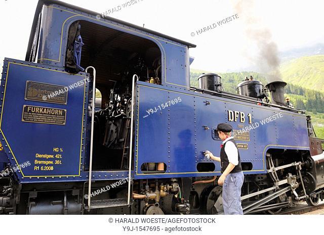 Boy polishing the Furka cogwheel steam railway engine at Realp station  Switzerland, Western Europe, Grimsel-/Furka region