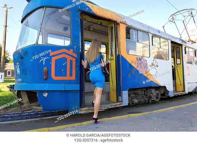 Beautiful, attractive Ukrainian woman wearing a blue dress going up to a tram in Zhitomyr, Ukraine