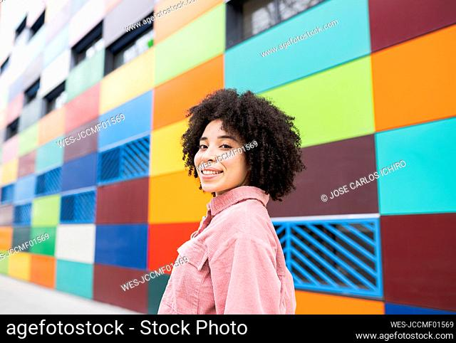 Curly hair woman smiling by colorful building