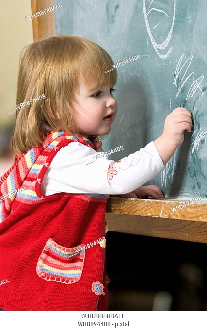 Profile of a baby girl writing on a blackboard