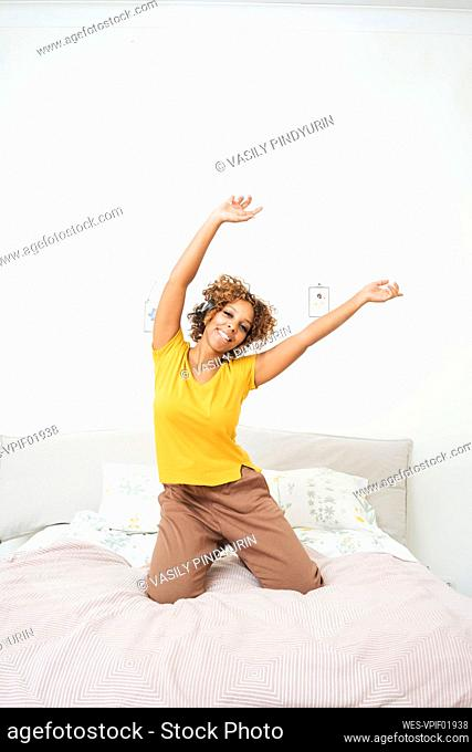Happy young woman listening to music with headphones on the bed at home