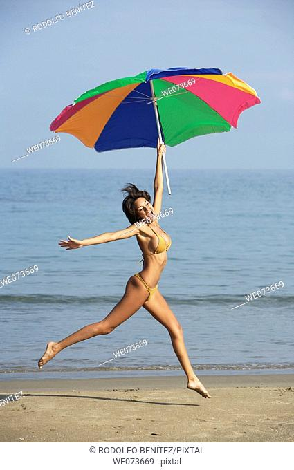 Latin girl jumping on the beach with an umbrella