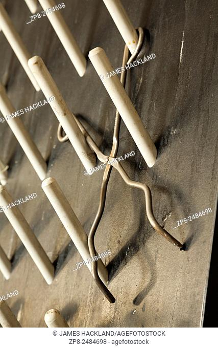 Chemistry tongs hanging on a peg board