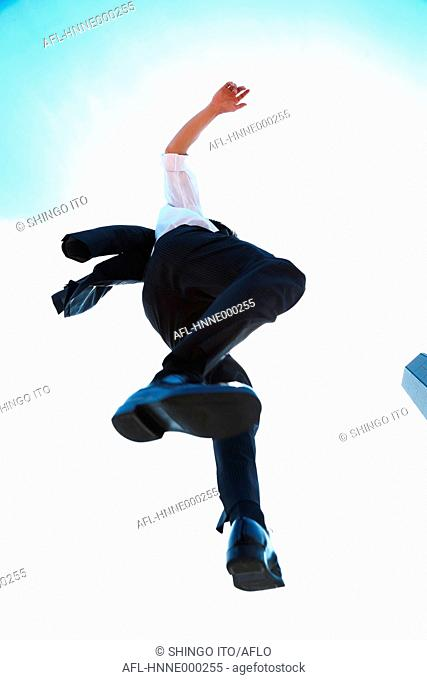 Young Japanese businessman jumping
