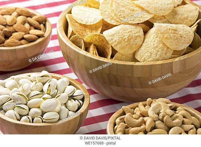 Close up of party bowls of potato chips, almonds, pistachios, and cashews on a red checkered tablecloth