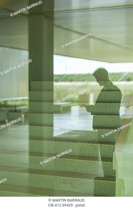Silhouette businessman texting with smart phone in office