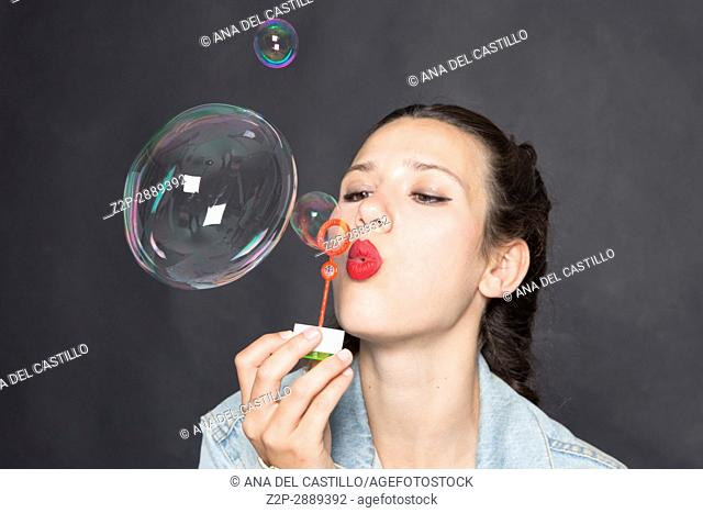 Mid-adult woman blowing bubbles
