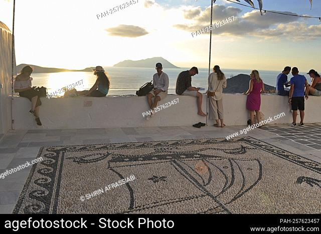 Vacationers, tourists sit on a white wall and enjoy the evening sun on the island of Milos / Greece. - Plaka/Griechenland