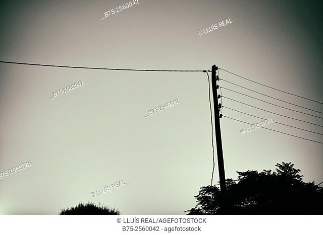 Silhouette of an electrical pole and electrical wires. Menorca, Biosphere Reserve, Balearic Islands, Spain, Europe