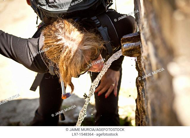 Woman drinking from a water fountain on the Camino de Santiago