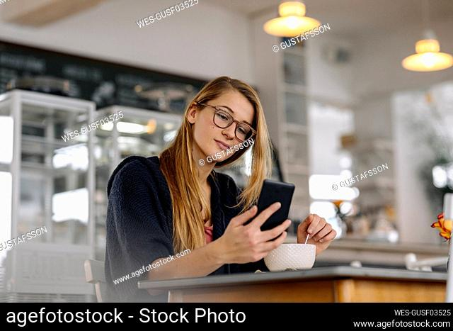 Young woman using smartphone in a cafe