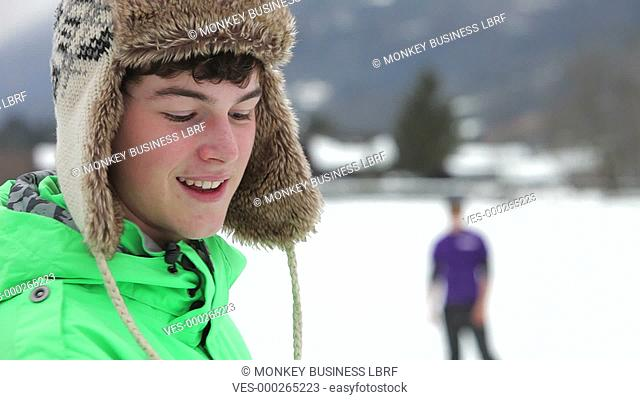 Teenage boy faces camera, tosses snowball in the air and then throws it at his friend in the distance.Shot on Canon 5D Mk2 at at a frame rate of 25 fps