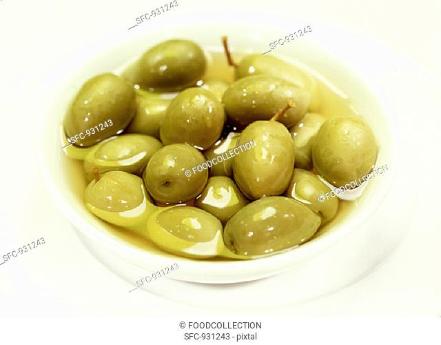 Pickled green olives in a small white bowl