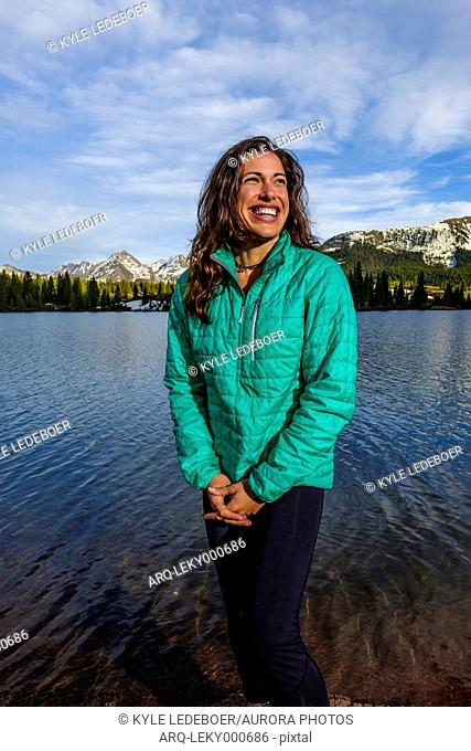 Portrait of adult woman standing against Molas Lake and smiling, Colorado, USA