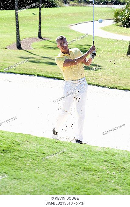 Caucasian man golfing from sand trap on golf course