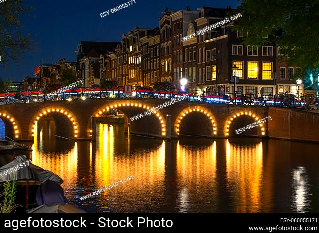 Netherlands. Illuminated canal at night in Amsterdam. Many bicycles are parked by the fence. Traditional houses with glowing windows