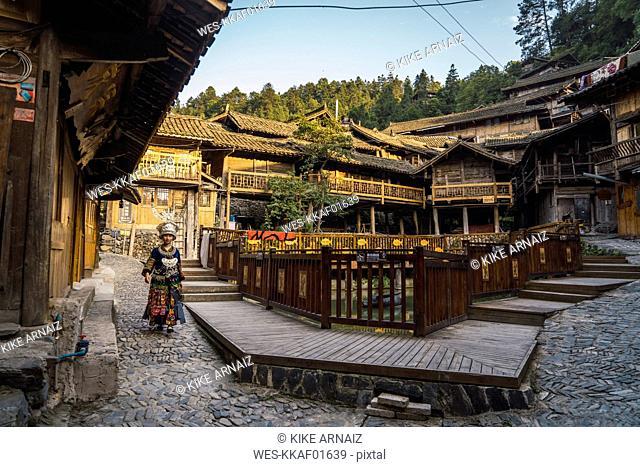 China, Guizhou, young Miao woman in traditional dress walking in a settlement