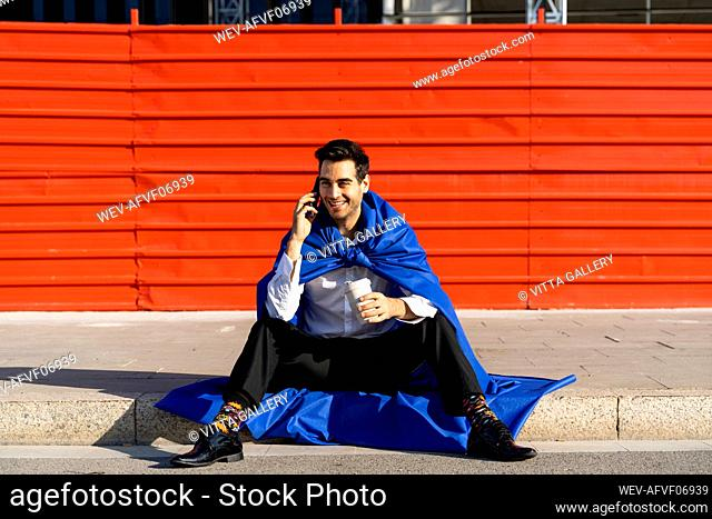 Smiling businessman on the phone wearing superhero cape sitting on curb
