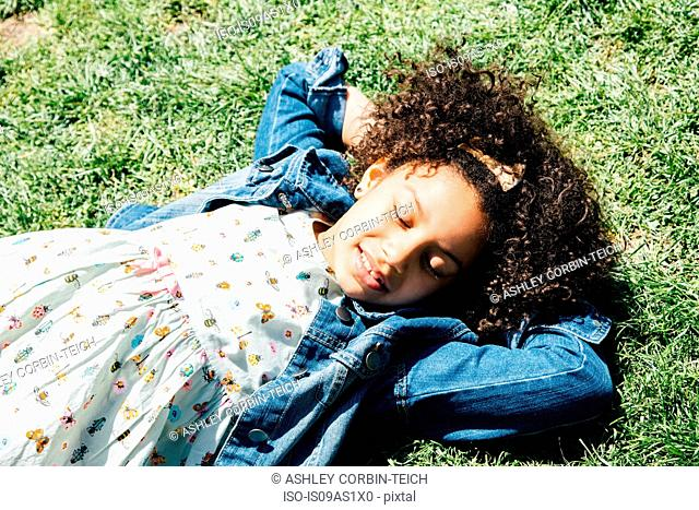 High angle view of girl lying on back on grass, hands behind head, eyes closed