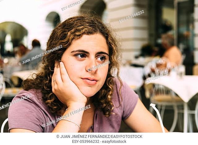 Young woman thinking while sitting on cafe. Concept yearning