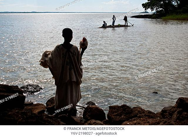 A traditionally dressed woman is waiting a papyrus boat to cross the Blue Nile river. ( She is holding a cock) In the background