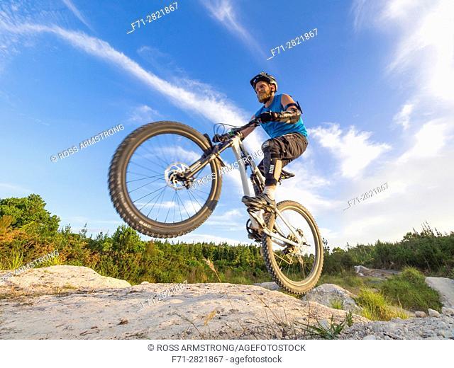 Male mountain biker doing jump with mountain bike on Parihaka Mountain Bike Track, Whangarei, New Zealand