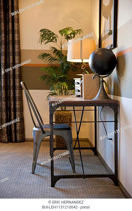 Side view of a chair at table with globe and lit lamp at home