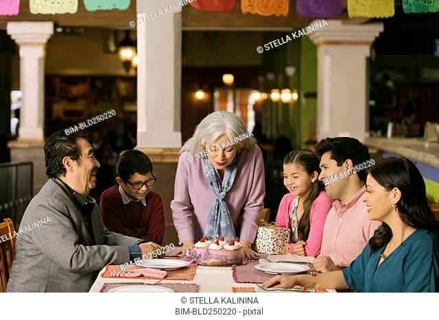Older woman blowing out candles on birthday cake in restaurant