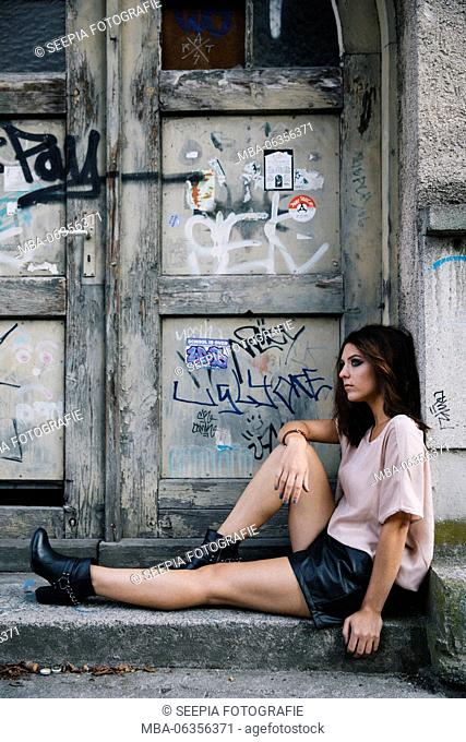 Young attractive brunette woman sits in front of door with graffiti