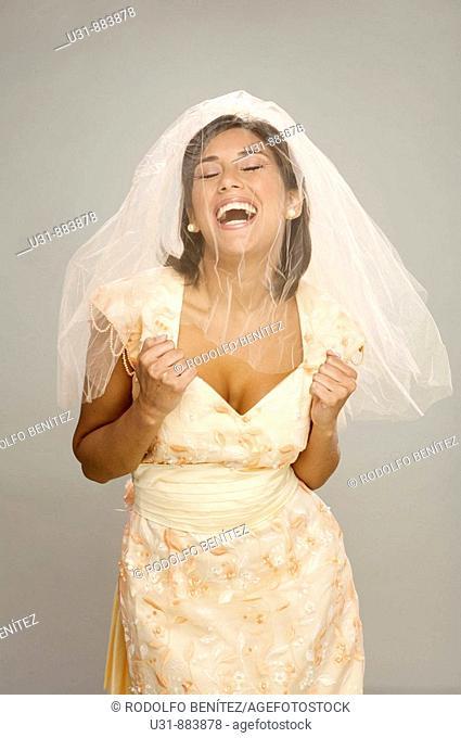 Bride in her 20s celebrates in a studio setting