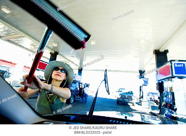 Japanese woman using squeegee on car windshield