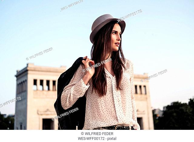 Portrait of young woman with long brown hair wearing hat looking at distance, Munich, Germany