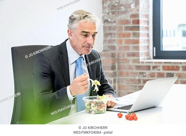 Mature businessman in office eating salad