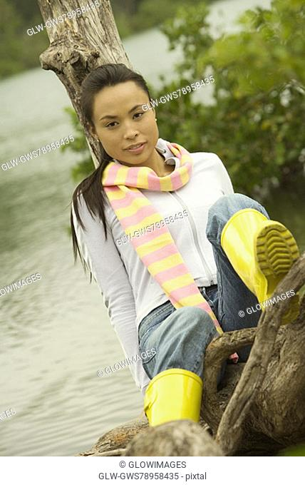 Portrait of a young woman sitting on a tree trunk by the lake