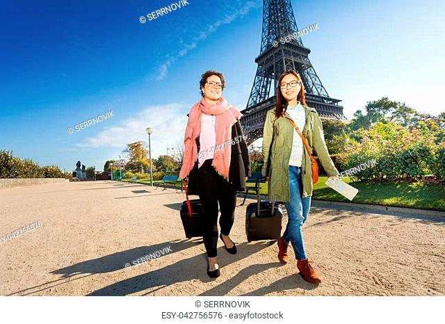 Two happy female tourists walking around Paris with their luggage