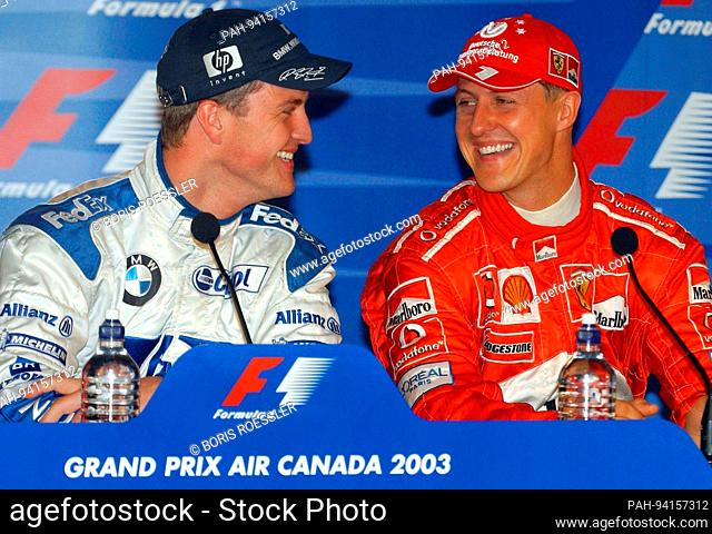 German brothers BMW Williams driver Ralf Schumacher and Ferarri driver Michael Schumacher share a joke at the press conference Saturday 14 June 2003 following...